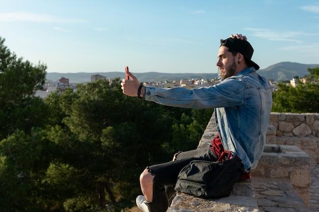 Jeune homme avec capuchon prend une photo avec la ville en arrière-plan.