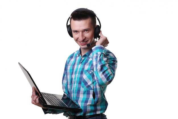 Jeune homme, à, casque à écouteurs, tenue, ordinateur portable, -, centre appel, homme, à, casque à écouteurs, et, ordinateur portable, sur, mur blanc