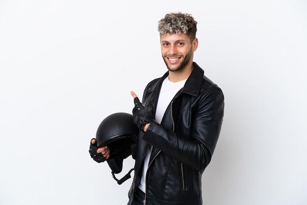 Jeune homme avec un casque de moto isolé sur fond blanc pointant vers l'arrière
