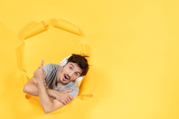 Jeune homme avec un casque pointant au-dessus sur fond de papier jaune musique ultrasonore audio