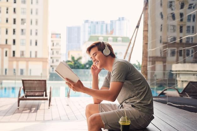 Jeune homme avec un casque près d'un livre de lecture de piscine