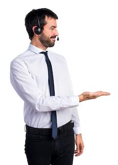 Jeune homme avec un casque présentant quelque chose