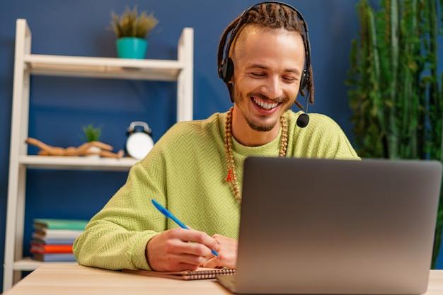 Jeune homme avec casque regardant la caméra de l'ordinateur portable. concept de consultant de service