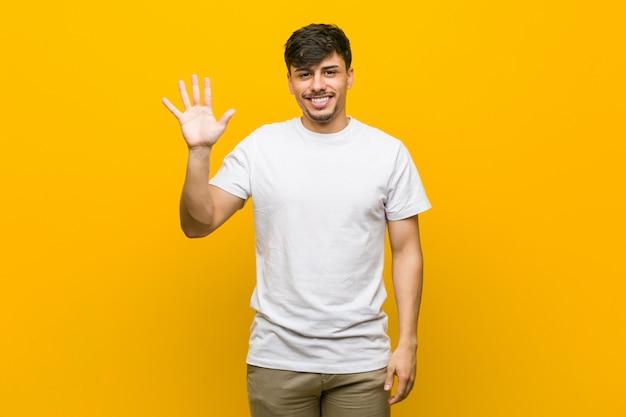 Jeune homme casual hispanique souriant joyeux montrant le numéro cinq avec les doigts.