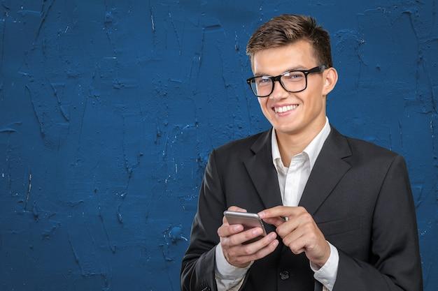 Jeune homme casual sms sur son smartphone