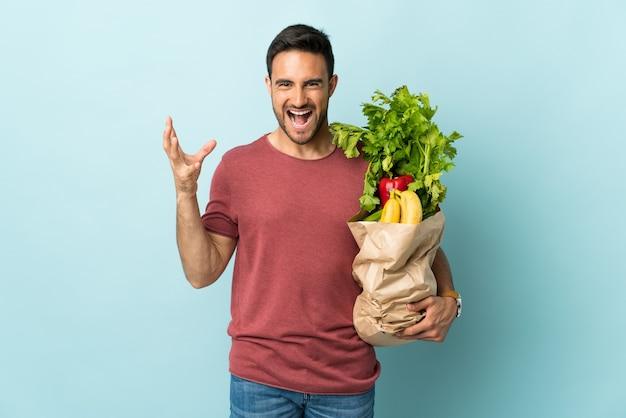 Jeune homme caucasien, acheter des légumes isolés sur fond bleu malheureux et frustré par quelque chose