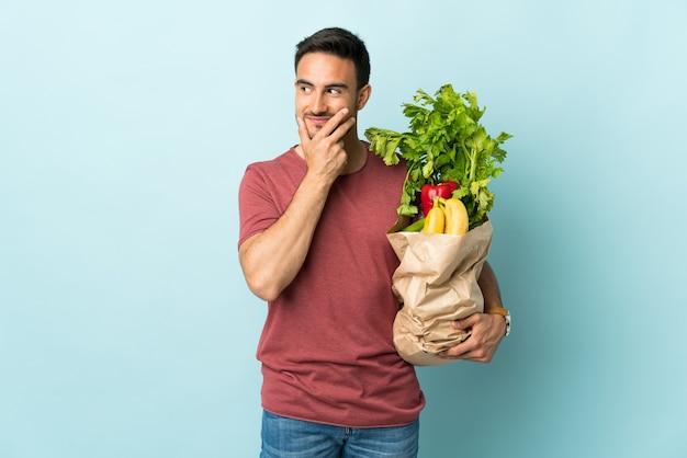 Jeune homme caucasien, acheter des légumes isolés sur fond bleu en pensant à une idée