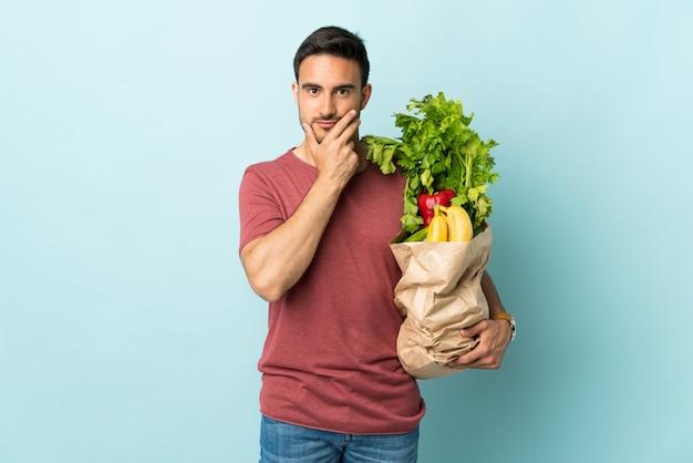 Jeune homme caucasien, acheter des légumes isolés sur un mur bleu en pensant à une idée