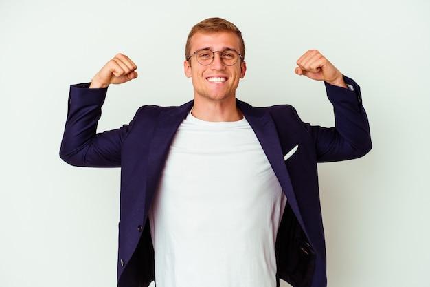 Jeune homme caucasien d'affaires isolé sur blanc montrant le geste de force avec les bras