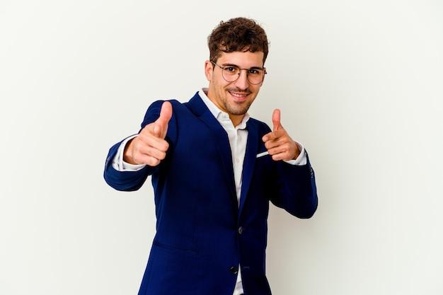 Jeune homme caucasien d'affaires isolé sur fond blanc pointant vers l'avant avec les doigts.