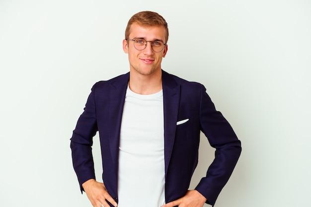 Jeune homme caucasien d'affaires isolé sur un mur blanc confiant en gardant les mains sur les hanches.