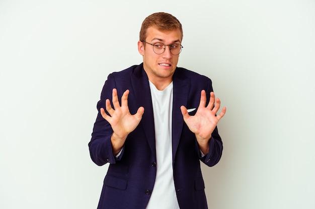 Jeune homme caucasien d'affaires isolé sur un mur blanc rejetant quelqu'un montrant un geste de dégoût.