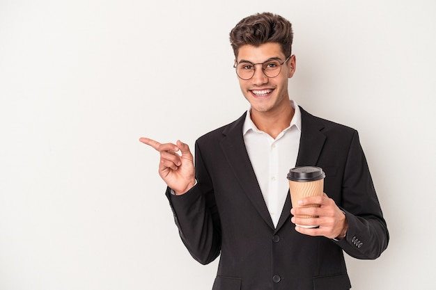 Jeune homme caucasien d'affaires tenant du café à emporter isolé sur fond blanc souriant et pointant de côté, montrant quelque chose dans un espace vide.
