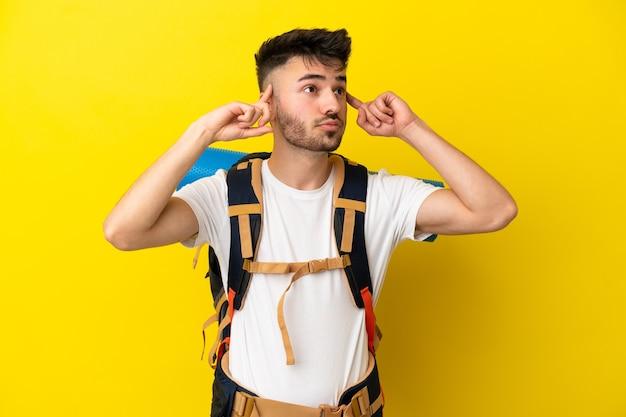 Jeune homme caucasien d'alpiniste avec un grand sac à dos d'isolement sur le fond jaune ayant des doutes et pensant