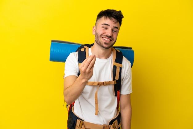 Jeune homme caucasien d'alpiniste avec un grand sac à dos d'isolement sur le fond jaune faisant le geste d'argent