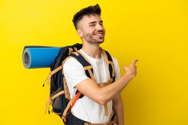 Jeune homme caucasien d'alpiniste avec un grand sac à dos d'isolement sur le fond jaune pointant en arrière