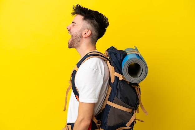 Jeune homme caucasien d'alpiniste avec un grand sac à dos d'isolement sur le fond jaune riant en position latérale
