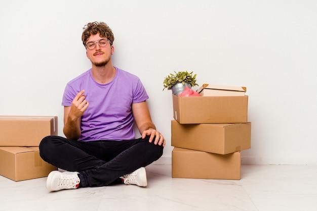 Jeune homme caucasien assis sur le sol prêt à se déplacer isolé sur fond blanc pointant du doigt vers vous comme s'il vous invitait à vous rapprocher.