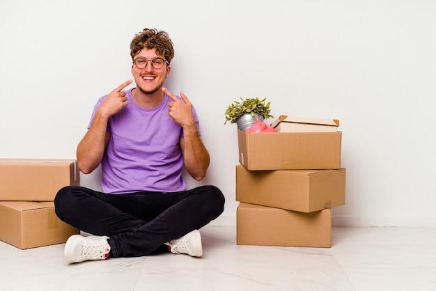 Jeune homme caucasien assis sur le sol prêt à se déplacer isolé sur fond blanc sourit, pointant du doigt la bouche.