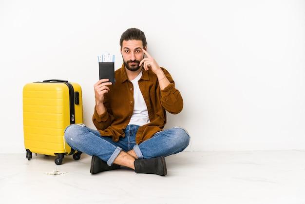 Jeune homme caucasien assis tenant un passeport et une valise isolé temple de pointage avec le doigt, la pensée, concentré sur une tâche