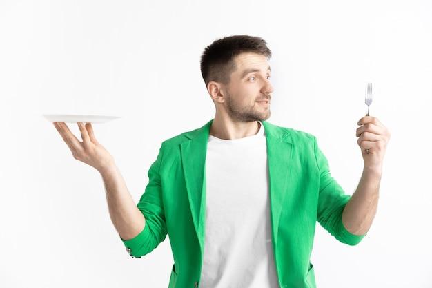 Jeune homme caucasien attrayant souriant tenant un plat vide et une fourchette isolé sur fond gris