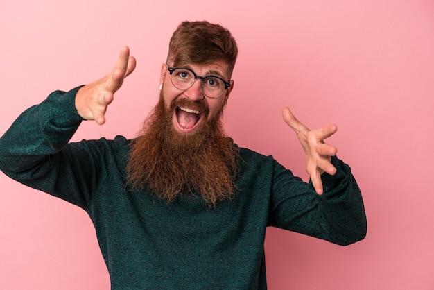 Jeune homme caucasien au gingembre avec une longue barbe isolé sur fond rose célébrant une victoire ou un succès, il est surpris et choqué.