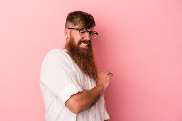 Jeune homme caucasien au gingembre avec une longue barbe isolé sur fond rose confus, se sent dubitatif et incertain.