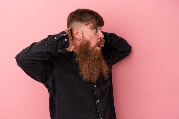 Jeune homme caucasien au gingembre avec une longue barbe isolé sur fond rose criant, très excité, passionné, satisfait de quelque chose.