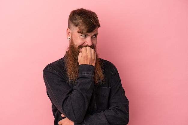 Jeune homme caucasien au gingembre avec une longue barbe isolé sur fond rose détendu en pensant à quelque chose en regardant un espace de copie.