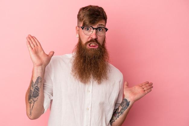 Jeune homme caucasien au gingembre avec une longue barbe isolé sur fond rose haussant les épaules confus et douteux pour tenir un espace de copie.