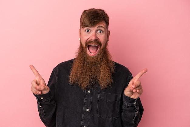 Jeune homme caucasien au gingembre avec une longue barbe isolé sur fond rose pointant vers différents espaces de copie, en choisissant l'un d'eux, montrant avec le doigt.