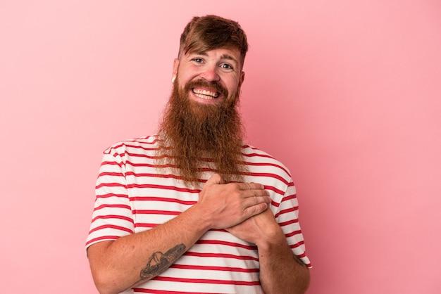 Le jeune homme caucasien au gingembre avec une longue barbe isolée sur fond rose a une expression amicale, pressant la paume contre la poitrine. notion d'amour.