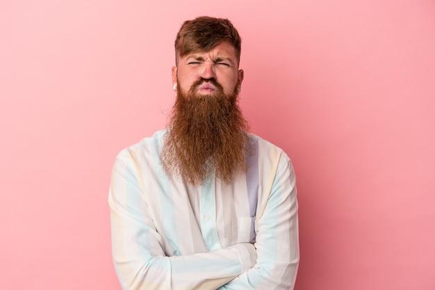 Jeune homme caucasien au gingembre avec une longue barbe isolée sur fond rose souffle les joues, a une expression fatiguée. concept d'expression faciale.