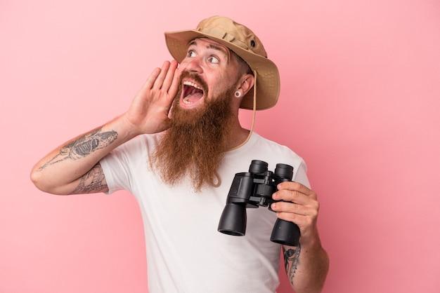 Jeune homme caucasien au gingembre avec une longue barbe tenant des jumelles isolées sur fond rose criant et tenant la paume près de la bouche ouverte.