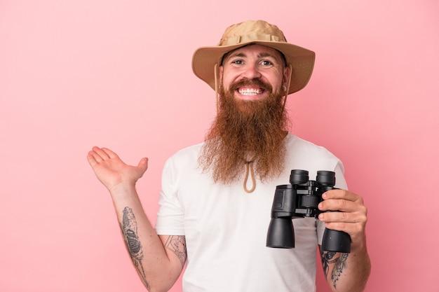 Jeune homme caucasien au gingembre avec une longue barbe tenant des jumelles isolées sur fond rose montrant un espace de copie sur une paume et tenant une autre main sur la taille.