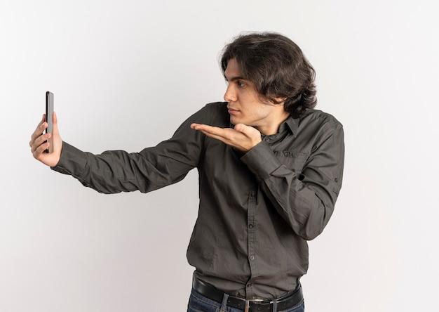 Jeune homme caucasien beau confus regarde et pointe le téléphone isolé sur fond blanc avec espace de copie