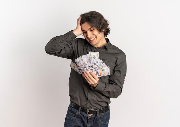 Jeune homme caucasien beau surpris met la main sur la tête tient et regarde l'argent isolé sur fond blanc avec espace de copie