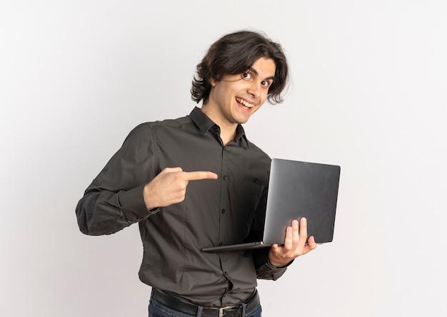 Jeune homme caucasien beau surpris tient et pointe sur un ordinateur portable isolé sur fond blanc avec espace de copie