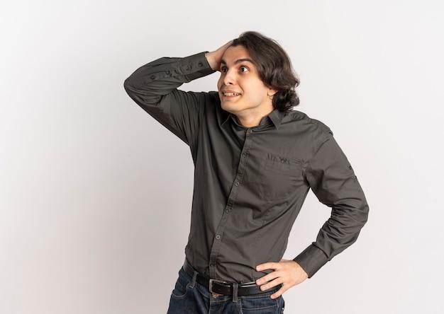Jeune homme caucasien beau surpris tient la tête et regarde le côté isolé sur fond blanc avec copie espace
