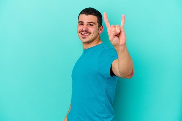 Jeune homme caucasien sur bleu montrant un geste de cornes comme un concept de révolution.