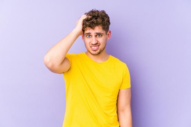 Jeune homme caucasien blond cheveux bouclés isolé fatigué et très endormi en gardant la main sur la tête.