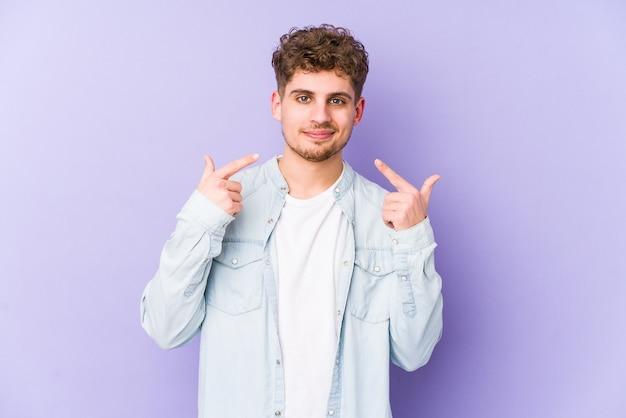 Jeune homme caucasien blond cheveux bouclés sourires isolés, pointant du doigt la bouche.