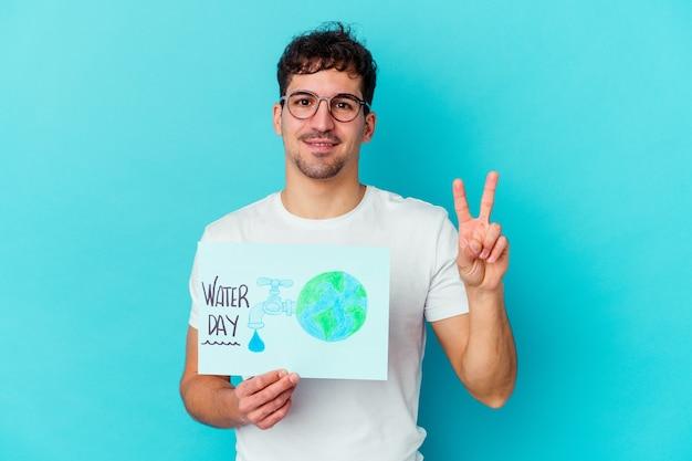Jeune homme caucasien célébrant la journée mondiale de l'eau isolée montrant le numéro deux avec les doigts.