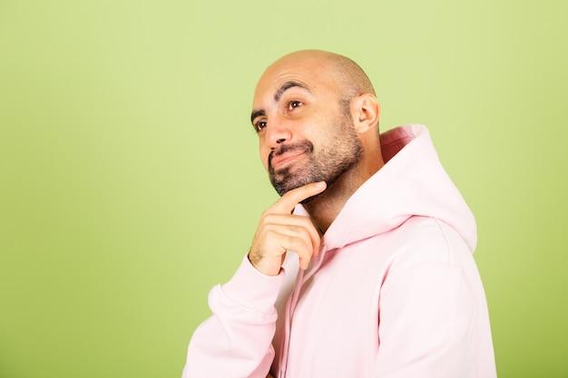 Jeune homme caucasien chauve en sweat à capuche rose isolé, inquiet d'une question, inquiet et nerveux avec la main sur le menton