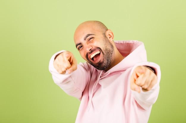Jeune homme caucasien chauve en sweat à capuche rose isolé, pointant vers vous avec les doigts, souriant positif et joyeux