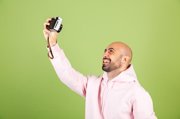 Jeune homme caucasien chauve en sweat à capuche rose isolé, positif gai prendre photo selfie sur appareil photo professionnel