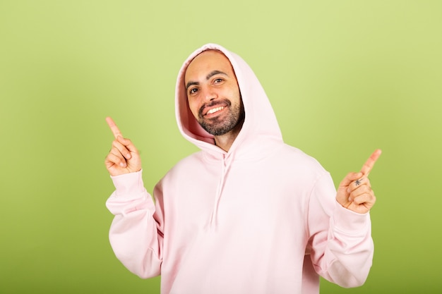 Jeune homme caucasien chauve en sweat à capuche rose pointer du doigt