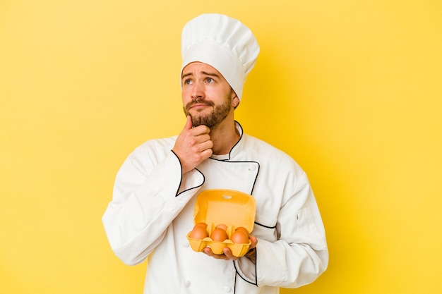 Jeune homme caucasien chef tenant des oeufs isolés sur fond jaune à la recherche de côté avec une expression douteuse et sceptique.