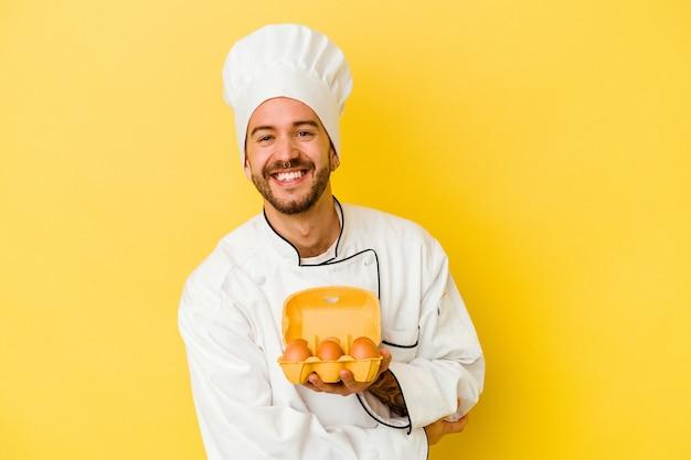 Jeune homme caucasien chef tenant des oeufs isolés sur fond jaune en riant et en s'amusant.