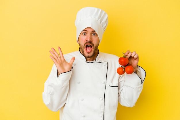 Jeune homme caucasien chef tenant des tomates isolés sur un mur jaune surpris et choqué.